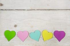 在老木白色破旧的别致的背景的五颜六色的心脏 免版税库存图片