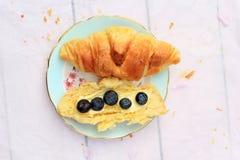 在老木背景的新鲜的新月形面包用新鲜的黄油和蓝莓 免版税库存图片