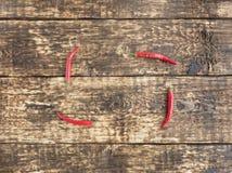 在老木背景的热的红辣椒辣椒 图库摄影