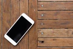 在老木背景的白色智能手机,顶视图 图库摄影