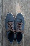 在老木背景的蓝色运动鞋 免版税库存照片