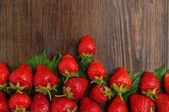在老木背景的许多鲜美草莓 免版税库存图片