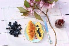 在老木背景,浪漫早餐的新鲜的法国新月形面包在庭院里 图库摄影