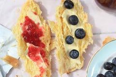 在老木背景,浪漫早餐的新鲜的法国新月形面包在庭院里 库存图片