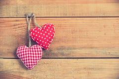 在老木背景,葡萄酒过程的两红色织品心脏 库存图片