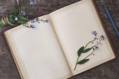 在老木背景说谎一个老笔记本和花束o 库存照片
