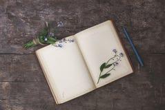 在老木背景说谎一个老笔记本和花束o 免版税库存图片