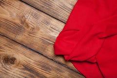 在老木被烧的桌上的红色backgr的洗碗布或委员会 库存照片