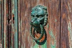 在老木门的狮子门把 免版税库存照片
