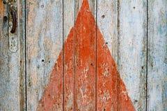 在老木门的被绘的红色三角与把柄 免版税图库摄影