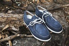 在老木头、灰色老石头和秋叶的时髦的蓝色绒面革人` s高帮皮马靴在森林或公园里 库存照片