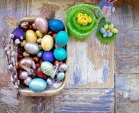 在老木破旧的桌上与绘的一个盘用与羽毛杨柳和鸡的不同的颜色复活节彩蛋用兔子 免版税库存照片