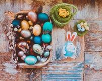 在老木破旧的桌上与绘的一个盘用与羽毛杨柳和鸡的不同的颜色复活节彩蛋用兔子 库存照片