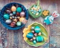 在老木破旧的桌上与绘的一个盘用与羽毛杨柳和鸡的不同的颜色复活节彩蛋用兔子 库存图片