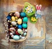在老木破旧的桌上与绘的一个盘用与羽毛杨柳和鸡的不同的颜色复活节彩蛋用兔子 免版税库存图片