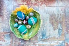 在老木破旧的桌上与绘的一个盘用与羽毛杨柳的不同的颜色复活节彩蛋 库存照片