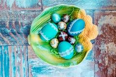 在老木破旧的桌上与绘的一个盘用与羽毛杨柳的不同的颜色复活节彩蛋 免版税库存照片
