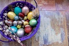 在老木破旧的桌上与绘的一个盘用与羽毛杨柳的不同的颜色复活节彩蛋 免版税图库摄影