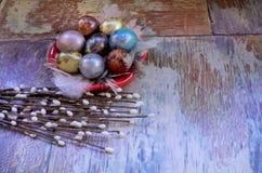 在老木破旧的桌上与绘的一个盘用与羽毛杨柳的不同的颜色复活节彩蛋 库存图片