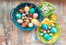 在老木破旧的桌上与绘的一个盘用与羽毛杨柳的不同的颜色复活节彩蛋 免版税库存图片