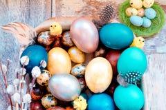 在老木破旧的桌上金属盘与绘的用与羽毛杨柳和鸡的不同的颜色复活节彩蛋 图库摄影
