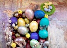 在老木破旧的桌上金属盘与绘的用与羽毛杨柳和鸡的不同的颜色复活节彩蛋 库存图片