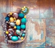 在老木破旧的桌上金属盘与绘的用与羽毛杨柳和鸡的不同的颜色复活节彩蛋 免版税库存图片