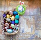 在老木破旧的桌上金属盘与绘的用与羽毛杨柳的不同的颜色复活节彩蛋用兔子 免版税库存照片