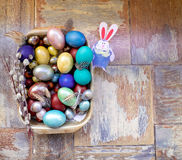 在老木破旧的桌上金属盘与绘的用与羽毛杨柳的不同的颜色复活节彩蛋用兔子 图库摄影
