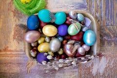 在老木破旧的桌上金属盘与绘的用与羽毛杨柳的不同的颜色复活节彩蛋 免版税库存图片
