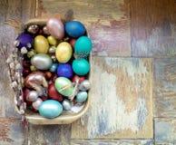 在老木破旧的桌上金属盘与绘的用与羽毛杨柳的不同的颜色复活节彩蛋 库存照片