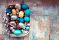 在老木破旧的桌上金属盘与绘的用与羽毛杨柳的不同的颜色复活节彩蛋 库存图片