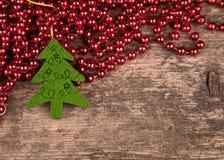 在老木头的红色珍珠与圣诞树 免版税图库摄影