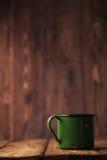 在老木头的葡萄酒绿色搪瓷杯子 免版税库存照片