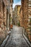 在老村庄法国使有花的被修补的街道狭窄 免版税库存图片