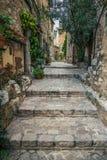 在老村庄,法国使有花的被修补的街道狭窄 免版税库存图片