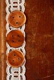 在老桌和鞋带上的三个手工制造木按钮 库存图片