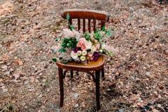 在老棕色椅子常设外部的美丽的婚礼花束在公园 库存图片