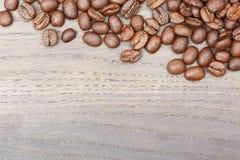 在老橡木桌上的咖啡豆边界 免版税库存照片
