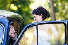 在老汽车的一对婚礼夫妇 免版税库存照片