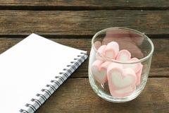 在老深褐色的板条的可爱的桃红色心脏蛋白软糖 库存照片