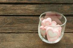 在老深褐色的板条的可爱的桃红色心脏蛋白软糖 免版税库存图片