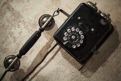 在老灰色混凝土墙上的葡萄酒黑电话 库存图片