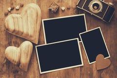 在老照相机和心脏旁边的空的照片框架 免版税库存图片