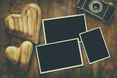 在老照相机和心脏旁边的空的照片框架 图库摄影