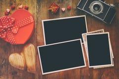 在老照相机和心脏旁边的空的照片框架 免版税库存照片