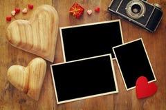 在老照相机和心脏旁边的空的照片框架 库存照片