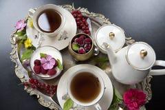 在老瓷杯子、panakota点心和莓的茶在一个老银色盘子 减速火箭 库存图片