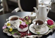 在老瓷杯子、panakota点心和莓的茶在一个老银色盘子 减速火箭 免版税库存照片