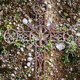 在老生苔墓碑的残破的铁耶稣受难象 库存照片